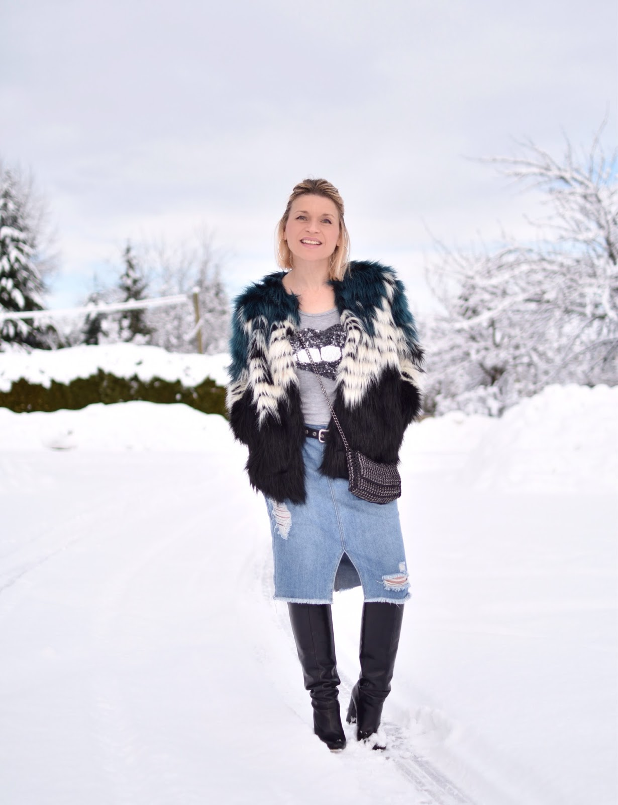 Monika Faulkner outfit inspiration - styling a distressed denim skirt with a sequinned tee, faux-fur jacket, and knee-high boots
