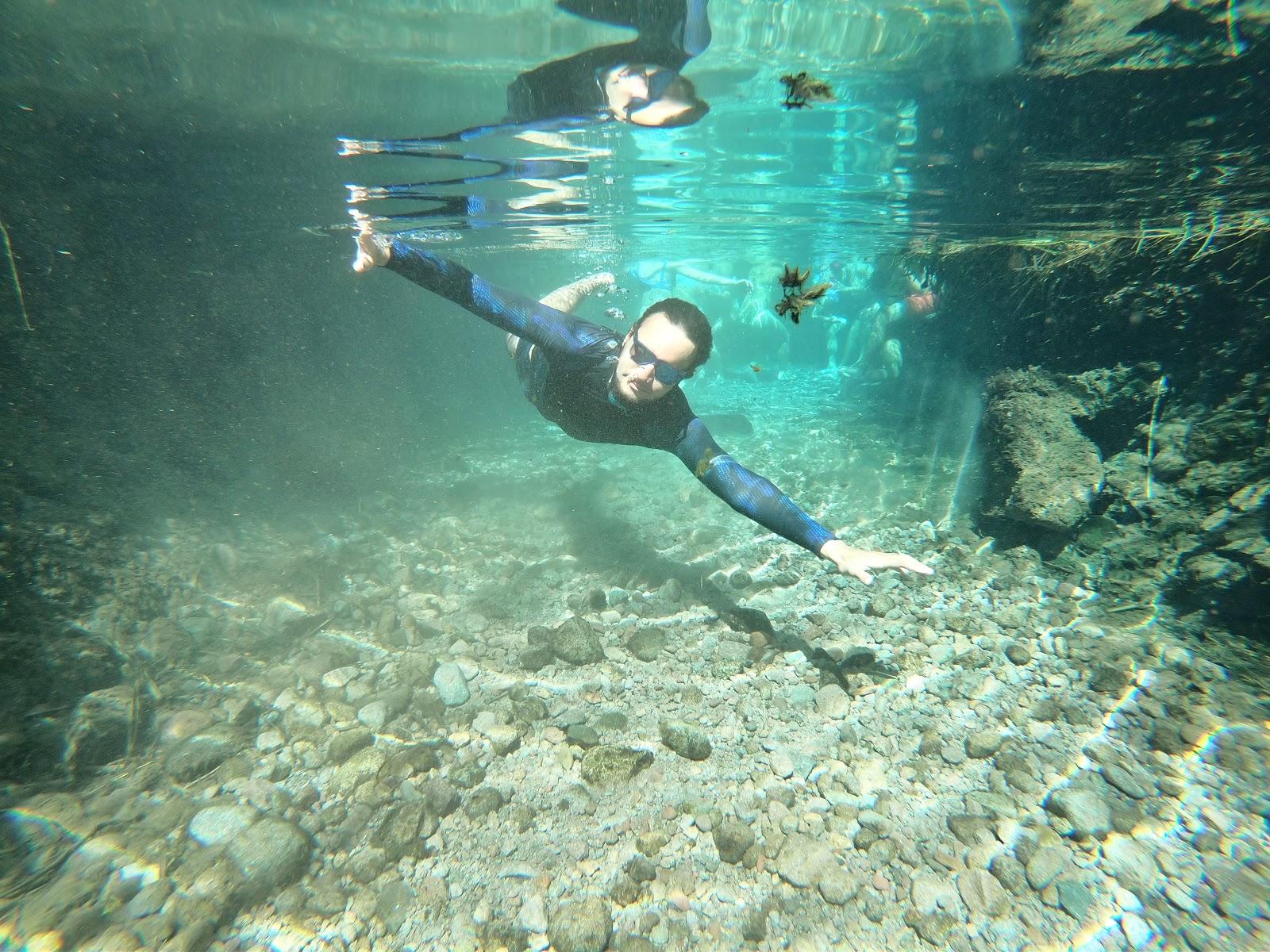 Homem nadando em águas transparentes dos Termas de Puritama.