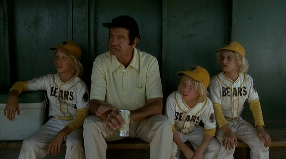 A scene from the bad news bears movie. One adult and three kids sitting in a dugout.