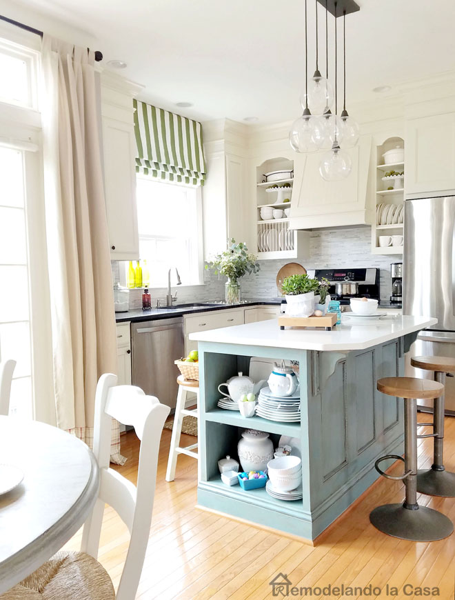 white kitchen with blue island and green shades