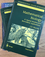 The two volumes of Mathematical Biology, by James Murray, superimposed on Intermediate Physics for Medicine and Biology.