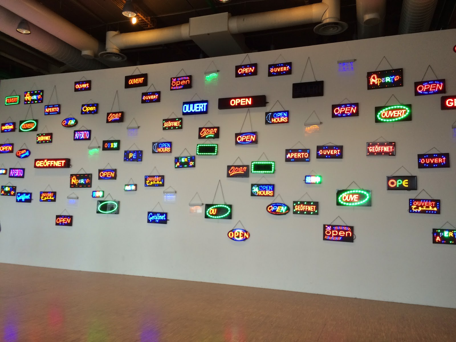 "Pic of neon-lit ""open"" signs in multiple languages at modern art gallery entrance"