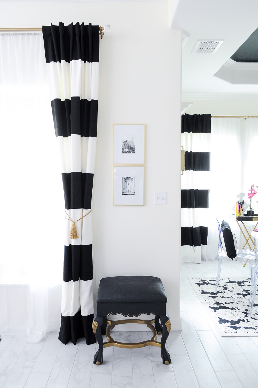Black and white striped curtains on a gold curtain rod in a bright white living room space.