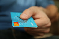 Picture of a person holding a credit card
