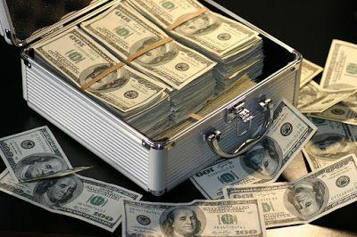 Maletín de dinero. Dólares en montones y billetes sueltos
