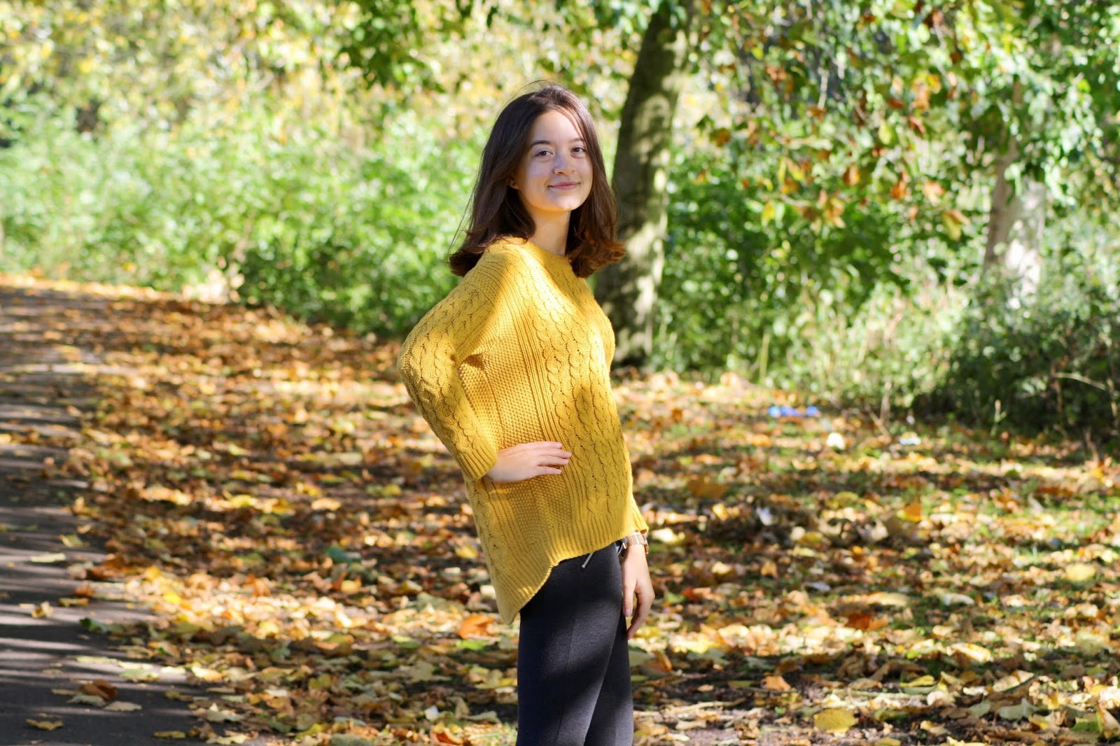 abbey stands turned towards the camera, hand on hip, she is smiling and wears a mustard knit jumper