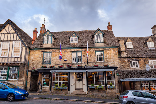 Historic building on the sloping street of Burford in the Cotswolds by Martyn Ferry Photography