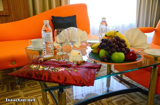 A table filled with welcoming fruits, water and goodies.