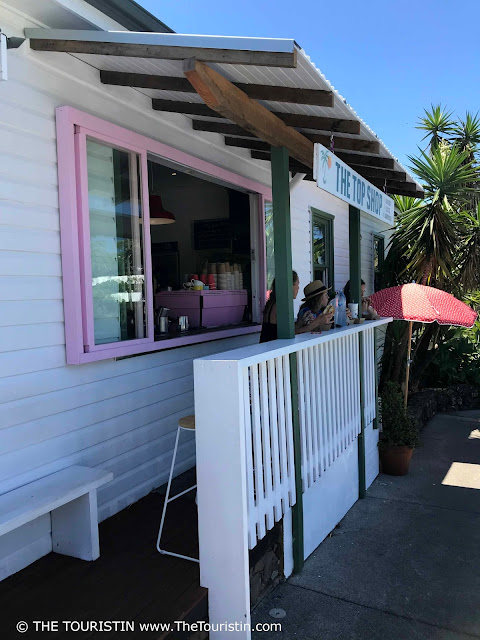 People drinking coffee on the verandah of a white weatherboard house with pink window frames.