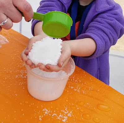 little hands full of play snow with water being poured in