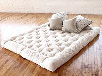 Parke üstünde serilmiş bir şilte yatak ve üzerindeki yastıklar