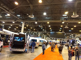several RVs on display at RV show with people walking around and looking at them