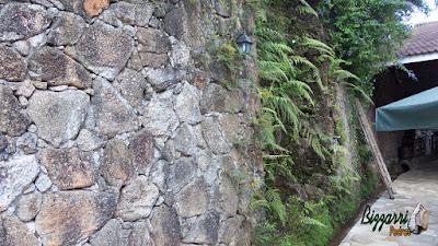 Muro de pedra com pedra moledo com a execução da cascata de pedra com a água caindo nas pedras em área de alimentação do Apiário Santo Antônio em Atibaia-SP com as mesas de madeira, as cadeiras de madeira e os guarda-sol.