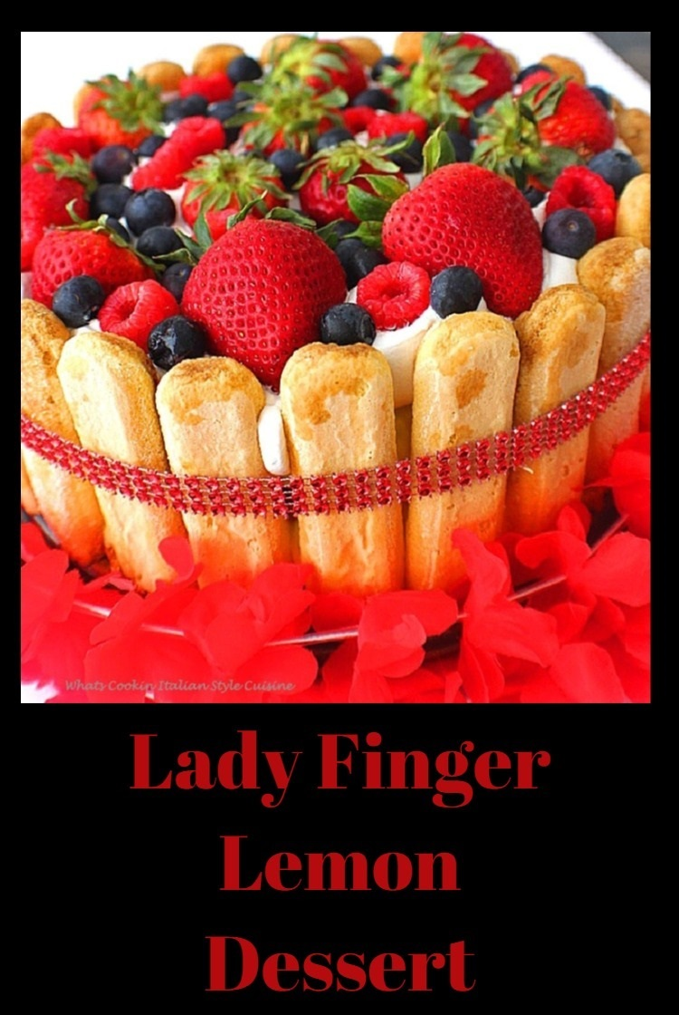 Decorated Red White and Blue lady fingers with sponge cake, lemon pudding and whipped cream adding blueberries and strawberries to the top for a 4th of july festive look and wrapped with a sparkling red beaded jewel ribbon for the 4th of July or Memorial Day Parties