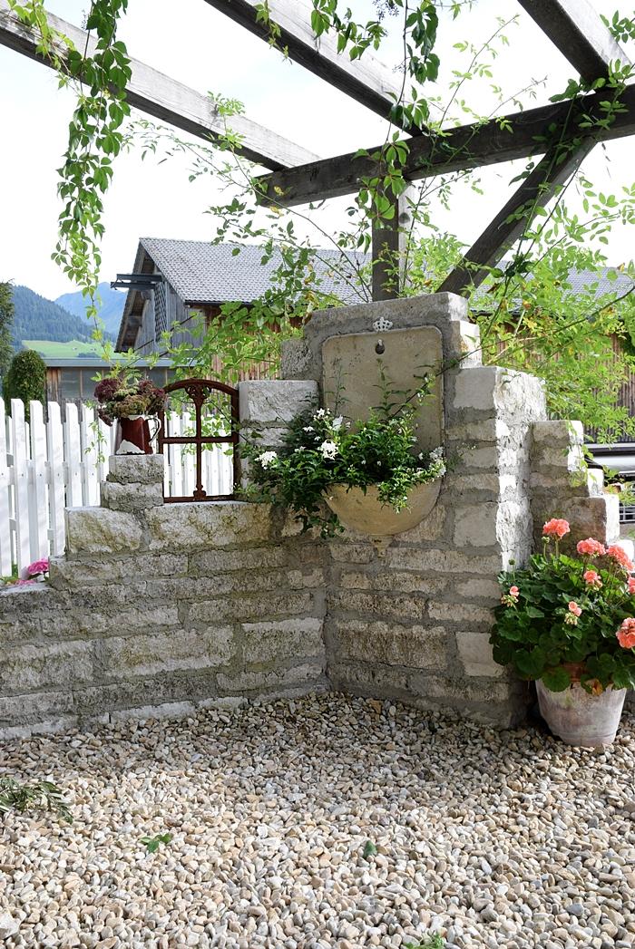 Selbstgebaute Ruinen-Gartenmauer mit Pflanzbrunnen