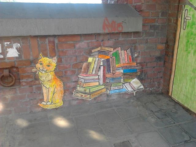 Кот и стопка книг лежащая на полу