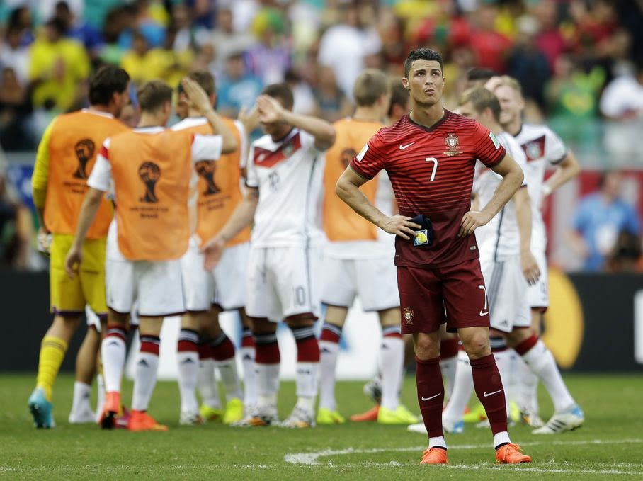 Portugal's Cristiano Ronaldo stands on the pitch as German players celebrate following Portugal's 4-0 loss to Germany during the group G World Cup soccer match between Germany and Portugal at the Arena Fonte Nova in Salvador, Brazil, Monday, June 16, 2014.