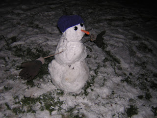[icture of medium sized snowman with knit cap, button eyes, carrot nose, and stick arms