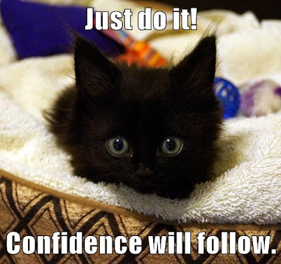 """A black kitten with large eyes stares intently into the camera. Text: """"Just do it! Confidence will follow!"""""""