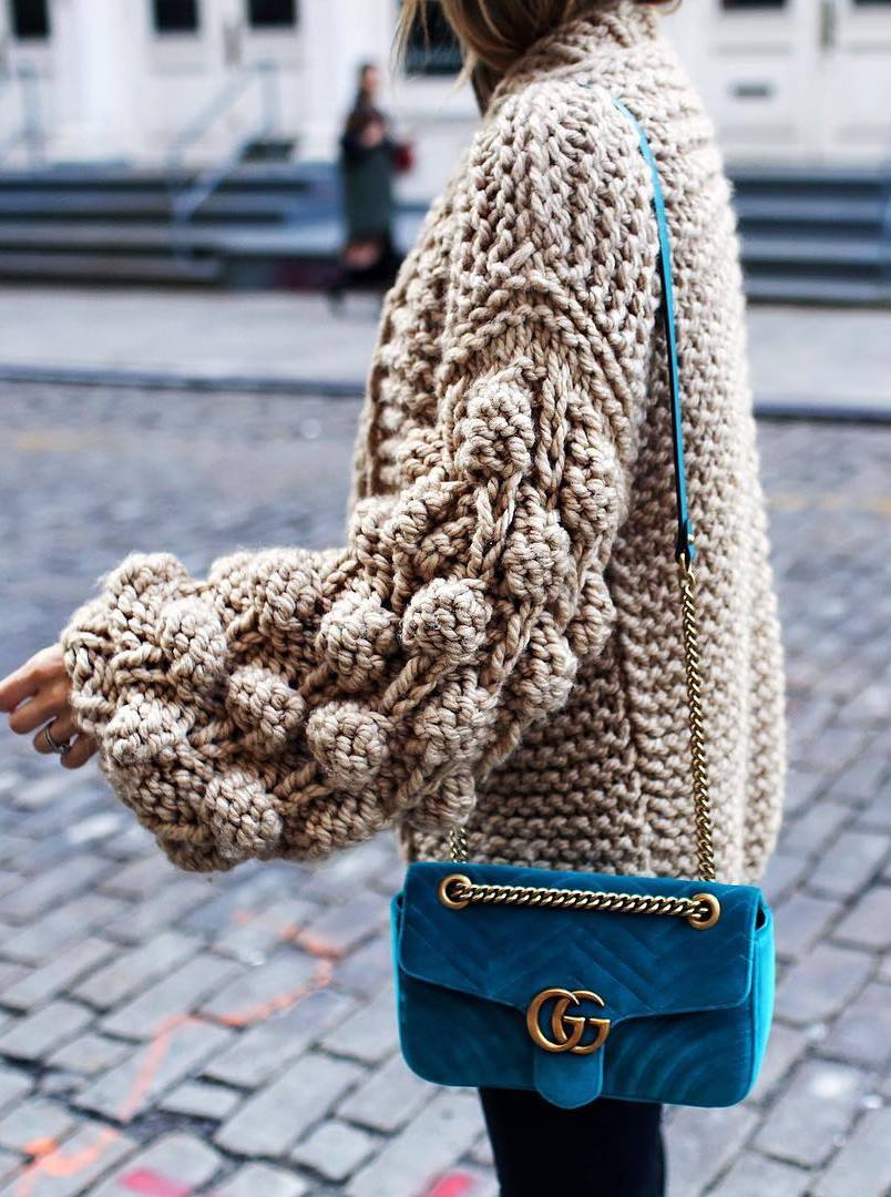 knit sweater and blue velvet bag