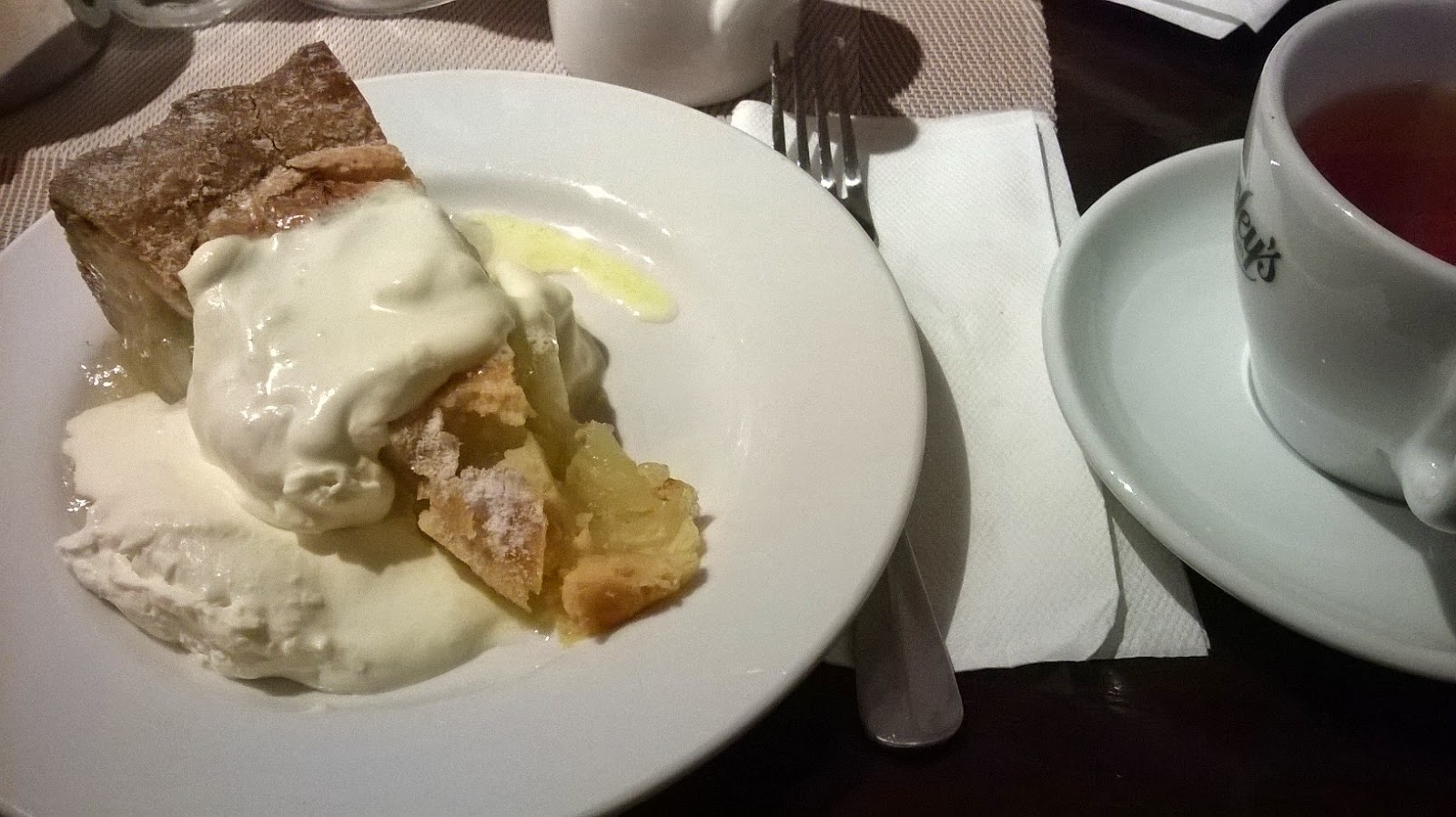 Torta di mele calda con panna montata e un thè inglese