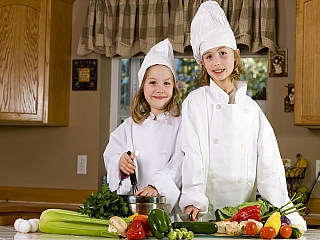 Two children learning how to cook dressed as chefs
