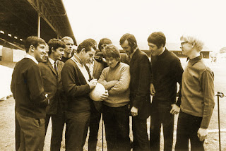 A photograph of Timebox receiving a signed football from some of the team members.