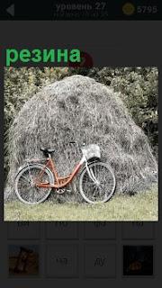 Небольшой стог сена около леса на поляне и рядом стоит велосипед с резиной на колесах