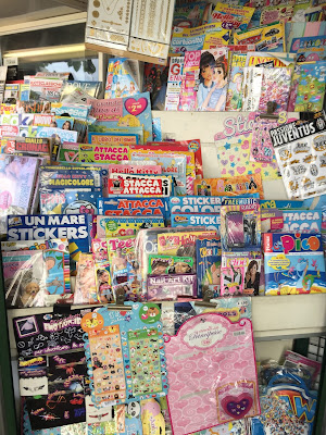 Stickers to peel off and stick on sale at a newsstand in Bergamo