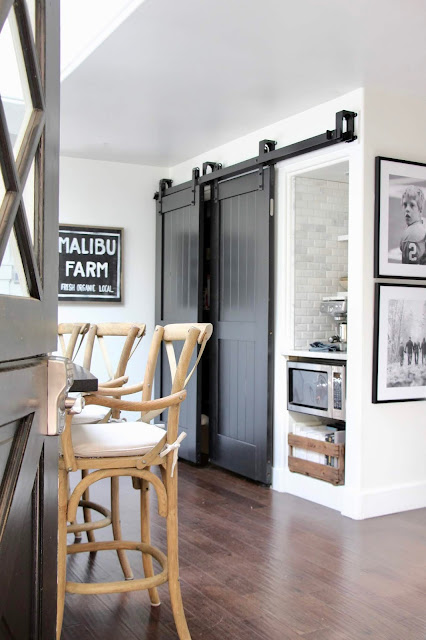 Black barn doors in a kitchen. Cozy cottage style with black and white in a lake house byy Sweet Savannah. Modern farmhouse meets coastal cottage style! #cottagestyle #modernfarmhouse #interiordesign #rusticdecor #coastalcottage