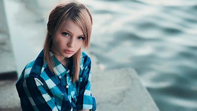 Chica rubia sentada al lado de un lago mirando a cámara