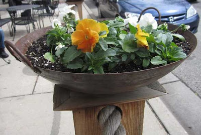 Rusted steel wok full of orange and white pansies, atop a wooden pillar