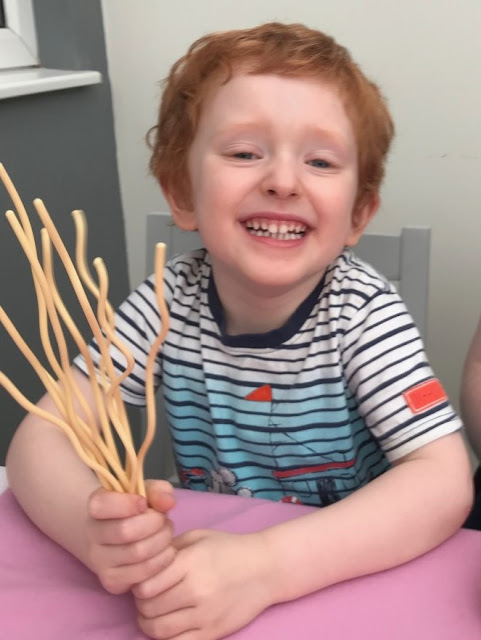 Smiling boy holding the plastic spaghetti
