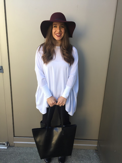blogger standing and smiling with burgundy wool floppy hat, berry lipstick, white top, black leggings and black leather boots.