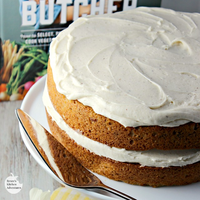 Parsnip Ginger Layer Cake with Browned Butter Frosting on cake platter with book in background