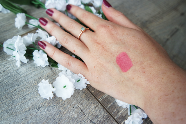 a swatch of rosy pink lipstick on a white hand with purple nails