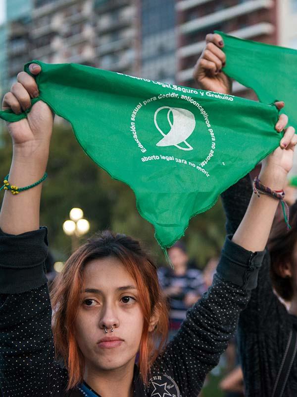 Una joven levanta un pañuelo verde a favor de la ley del aborto legal, seguro y gratuito