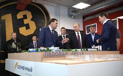 Vladimir Putin inspects a scale model of the sports and educational cluster to be constructed in Yekaterinburg's new neighborhood.