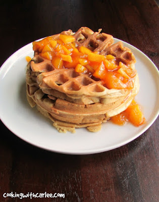 stack of waffles drizzled with cooked peach sauce