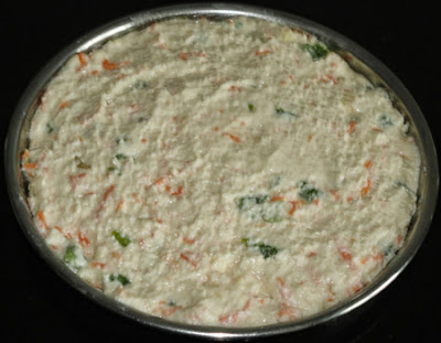 Batter spread in a plate to make rava dhokla
