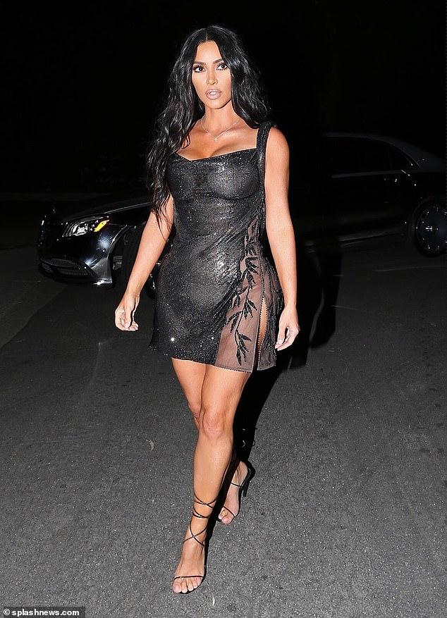 Kim Kardashian puts on a cheeky display in slightly sheer vintage Versace mini dress