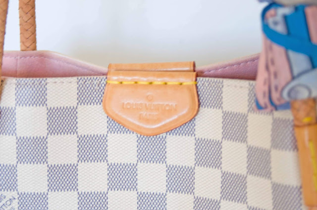 emblemat Louis Vuitton wybite logo na zapięciu torebki