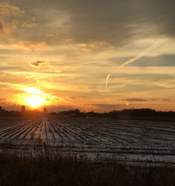 sunset across a partially snow-covered field