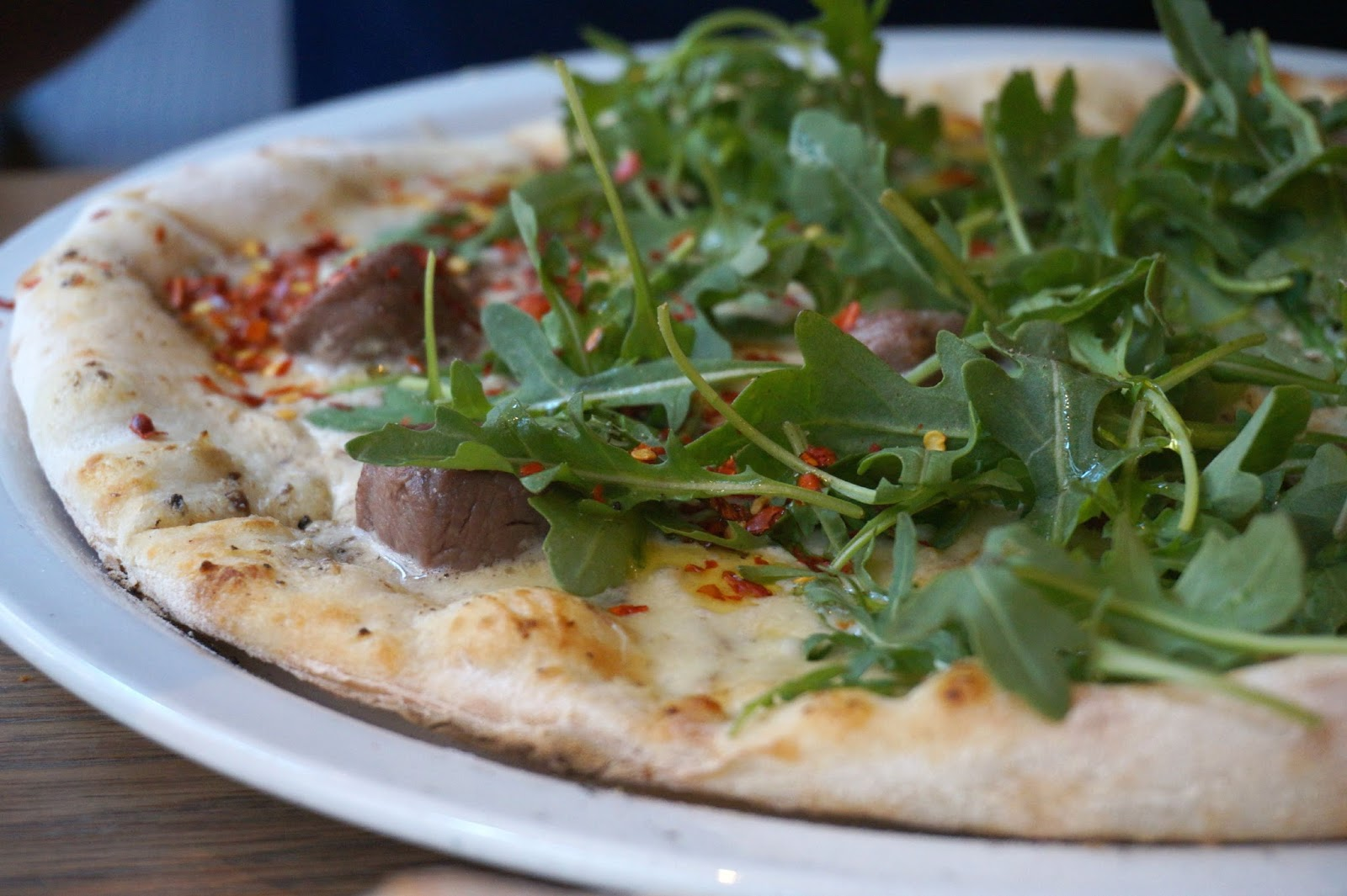 pizza with meat and fresh rocket