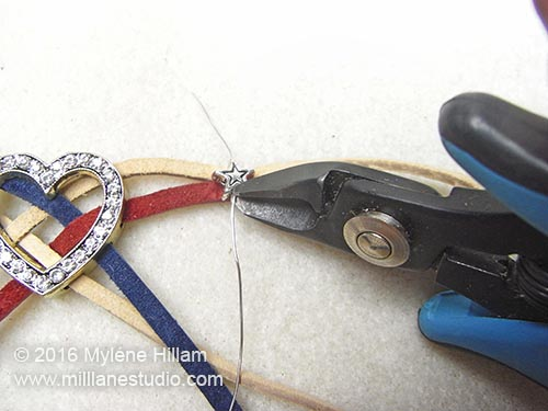 Using flush cutters to cut the excess wire close to the bead.