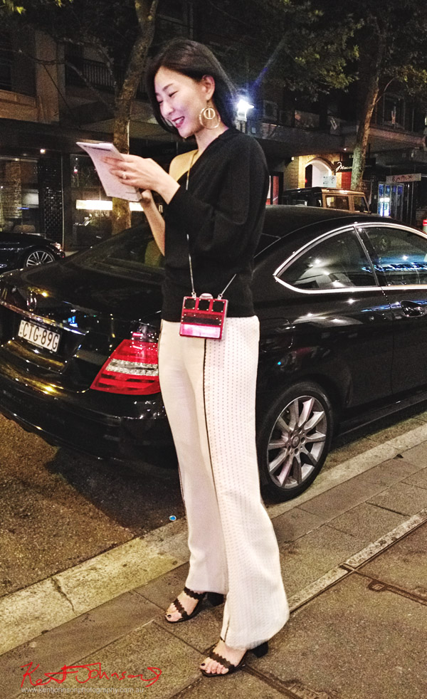 Asymmetick off shoulder black top, slacks with balck detail and red disco bag. Photographed by Kent Johnson for Street Fashion Sydney.