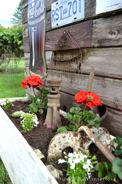 rusty garden tools leaning against a rustic shed as garden art, inside a flowerbed with red geraniums