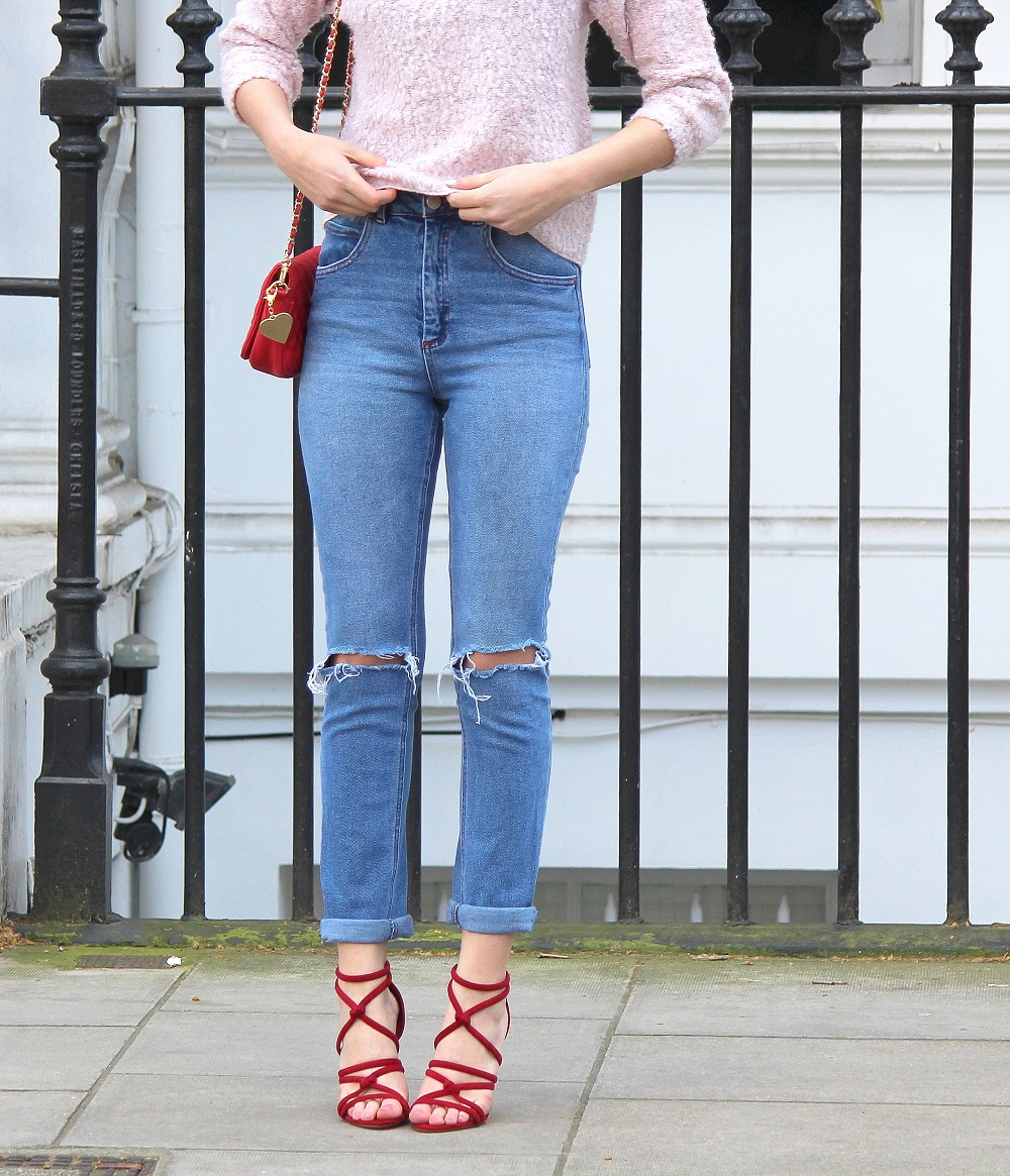 peexo fashion blogger wearing ripped mom jeans and red strappy heels and red small bag and pink fluffy jumper in spring