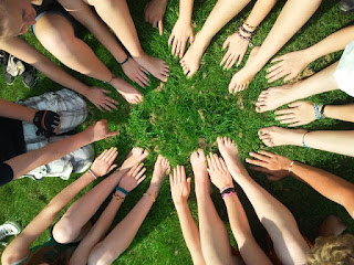 A circle of hands and feet of many people, laid on grass