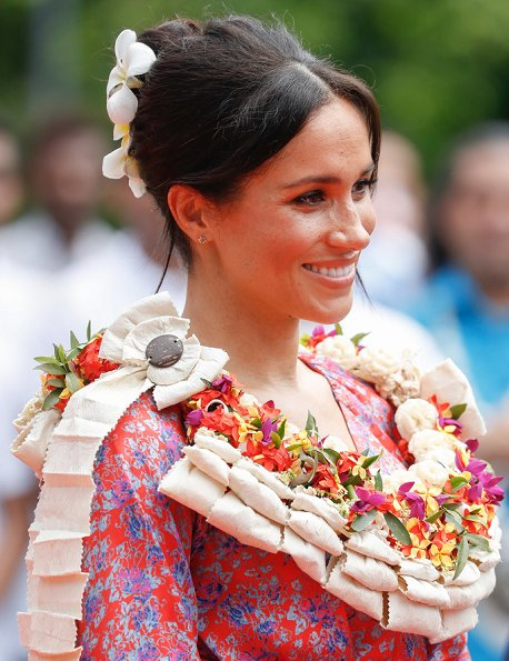 Meghan Markle wore Figue Frederica printed ruffle dress and Castañer Carina Black canvas wedge, and she wore Karen Walker gold stud earrings